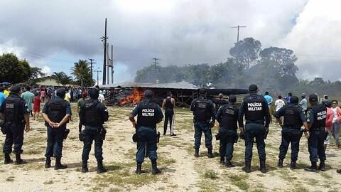 Des policiers et des habitants regardent un camp de migrants en flammes.
