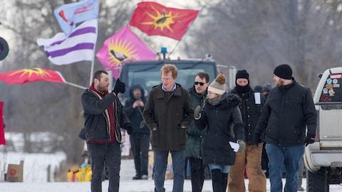 Un groupe de personnes marchent dans la neige près de voies ferrées où des drapeaux autochtones flottent dans le vent.