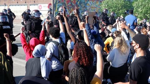De jeunes manifestants noirs et blancs lèvent un bras face à un groupe de policiers anti-émeutes.