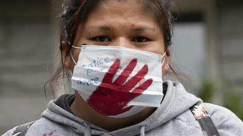 Une femme porte un masque où l'on peut lire : Justice pour Joyce.