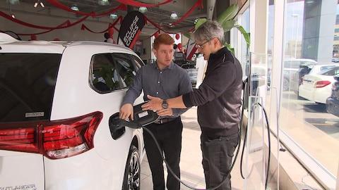 Un vendeur présente une voiture électrique à un client chez un concessionnaire automobile.