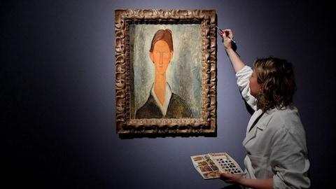 Peinture d'un portrait d'une femme accroché au mur. Une employée en sarrau blanc tient dans sa main un fin pinceau.