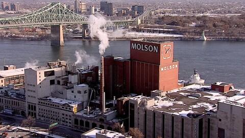 Vue aérienne de l'usine de Molson, avec le fleuve Saint-Laurent et le pont Jacques-Cartier en arrière-plan.