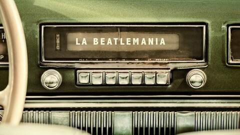 Une radio d'une vieille voiture avec la légende « La Beatlemania ».