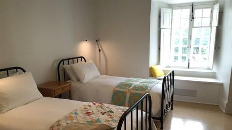 Deux lits simples dans une chambre avec une grande fenêtre