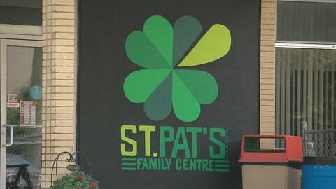 L'enseigne du centre illustrée d'un trèfle vert recouvre une partie de la façade à l'entrée de l'édifice.