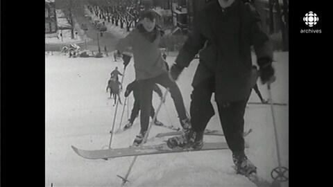 File de skieurs montant la pente enneigée du mont Royal à l'aide de bâtons
