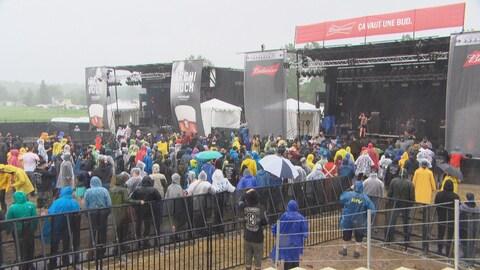 Une centaine de personnes vêtues de manteaux de pluie écoutent un concert rock extérieur, sous la pluie.
