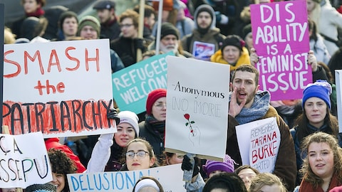 Des manifestants brandissent leurs pancartes à la Marche des femmes de Montréal le 20 janvier 2018.
