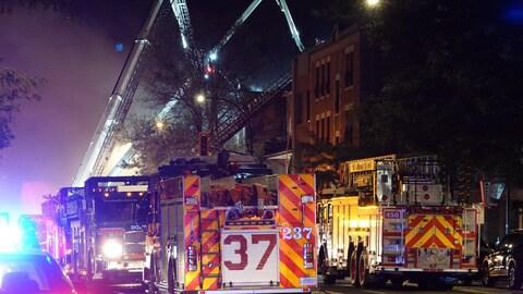 Des camions de pompiers avec la grande échelle déployée.