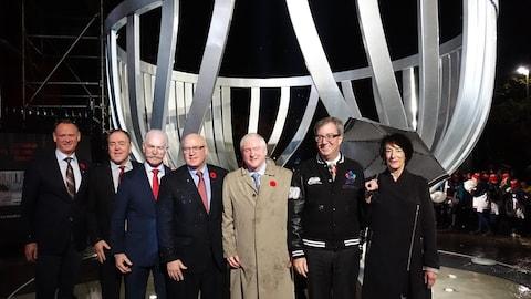 De gauche à droite: David McGuinty, député fédéral d'Ottawa-Sud; Tom Anselmi, directeur général des Sénateurs d'Ottawa; Lanny McDonald, président du Temple de la renommée du Hockey; Bill Daly, adjoint au commissaire de la LNH; George Hunter, président de Monument Mémorial Lord Stanley; Jim watson, maire d'Ottawa; et Linda Covit, une des artistes qui a conçu le monument; devant le monument en hommage à la coupe Stanley.