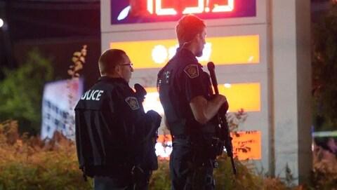 Deux policiers se tiennent devant le panneau d'une station service.