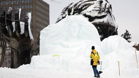 Un homme, de dos, observe la sculpture d'une femme à la longue chevelure qui prend forme dans le bloc de neige devant lui.
