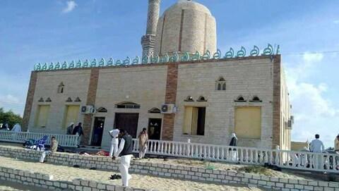 Des gens marchent devant une mosquée.