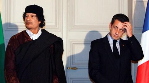 L'ancien chef libyen porte une toge et l'ancien président français, en costume, se touche le front.