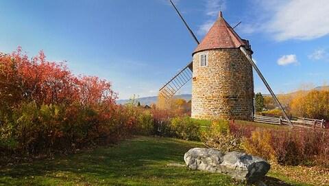 Un moulin patrimonial en pierre est situé sur une colline, face au fleuve Saint-Laurent.
