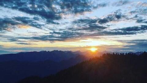 Un coucher de soleil plombe au-dessus de pics montagneux.