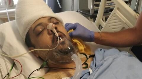 Photo d'un homme couché dans un lit d'hôpital et branché à un respirateur