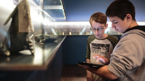 Deux élèves consultent une tablette informatique dans un musée