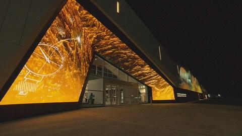 La devanture d'un musée prise le soir est illuminée par un écran de projection aux teintes dorées.