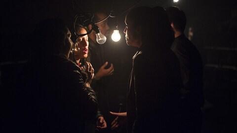 Les chanteurs dans le noir autour d'une lampe qui éclaire seulement leurs visages.