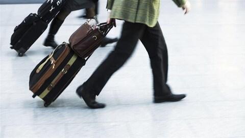 Deux personnes marchent avec des valises sur un plancher d'aéroport.