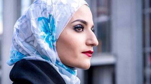 Portant un voile bleu sur ses cheveux, la jeune femme regarde l'horizon.