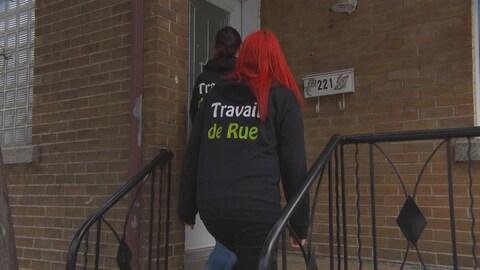 Deux femmes portent un chandail écrit Travail de rue. Elles montent les escaliers d'une maison.