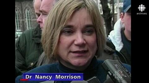 La femme est entourée de journaliste à sa sortie du palais de justice.