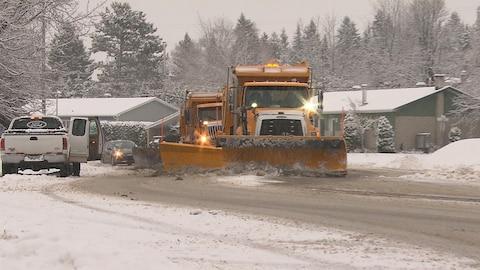 Deux chasse-neige sont à l'oeuvre sur une rue, tandis que la neige continue à tomber.
