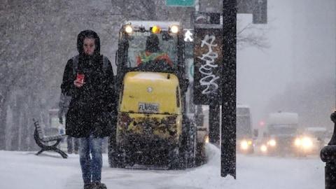 Une femme marche dans la rue sous la neige