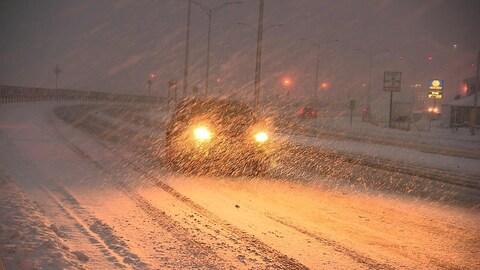 Une voiture sur la route dans une tempête de neige