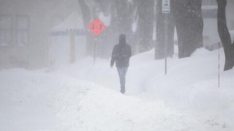 Un piéton sur un trottoir enneigé à Québec.