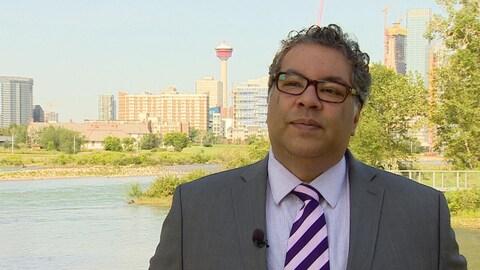 Un homme en costume cravate debout sur la berge de la rivière Bow avec Calgary en arrière-plan.