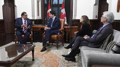 Les quatre politiciens discutent, assis dans un bureau.