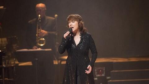 Nicole Martin chante devant un saxophoniste.