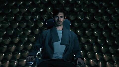 Un homme assis regarde devant lui, l'air inquiet, dans une scène de la série «Nightflyers».