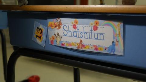 Le mot shatshitun écrit sur le devant d'un pupitre d'élève du primaire.