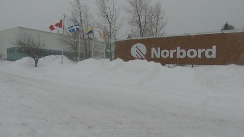 Le nom de Norbord est inscrit en blanc sur l'usine. Il y a quatre drapeaux derrière.