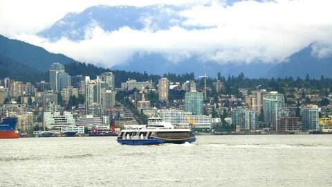 Des tours d'habitation devant un horizon montagneux avec, en avant-plan, une étendue d'eau sur laquelle circule un navire.