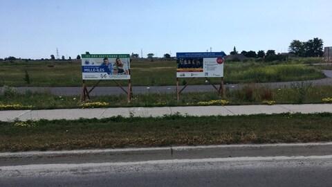 Deux affiches sur un terrain vague.
