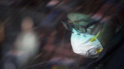 Un homme portant un masque afin d'éviter une infection virale.