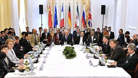 De nombreuses personnes sont assises autour d'une grande table.