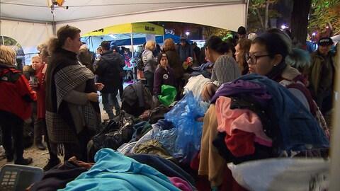 Des gens sous une tente autour d'une table pleine de vêtements