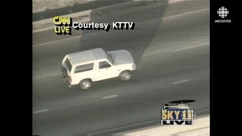 Vue aérienne de la camionnette Ford Bronco blanche qui roule sur l'autoroute. En surimpression à l'écran, les logos des sources de la diffusion: CNN, KTTV et SKY 11.