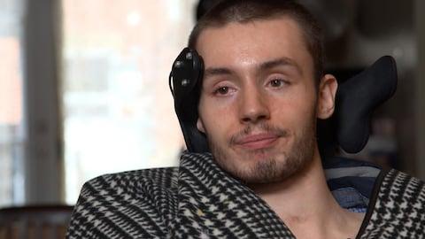 Olivier Gingras parle à la caméra dans sa chaise roulante.