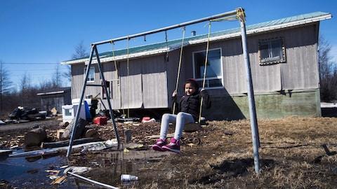 Une jeune fille se balance dans une réserve autochtone à Attawapiskat, en Ontario.
