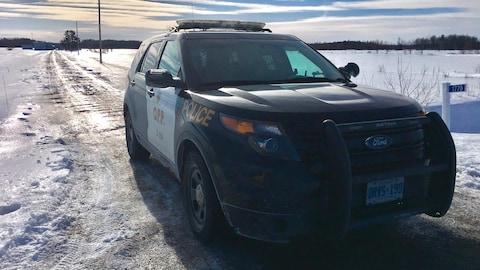 La voiture de police est stationnée le long d'un chemin de campagne