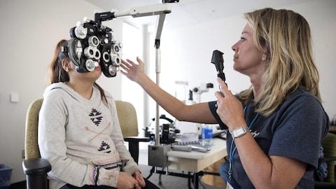 Une optométriste effectue un examen de la vue sur une jeune fille.