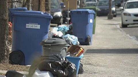 Des ordures ménagères et des matières recyclables sur le bord d'une rue.